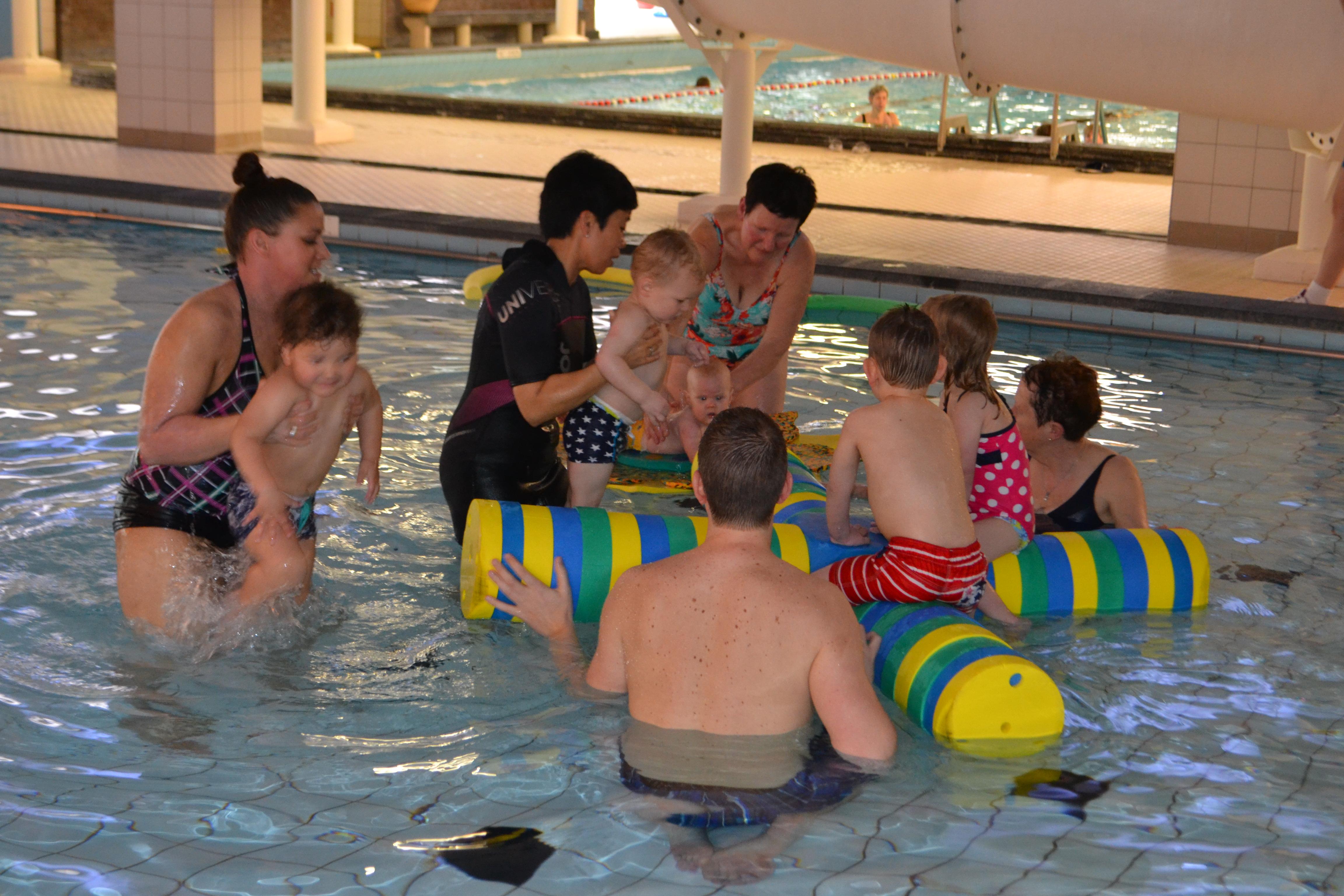 Ouders met kinderen en een instructrice tijden het ouder en kind-zwemmen in het Lentebad in Zevenaar.