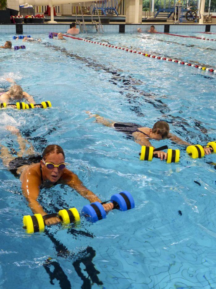 Lentebad - trimzwemmen, zwembad, zwemmende mensen met halters